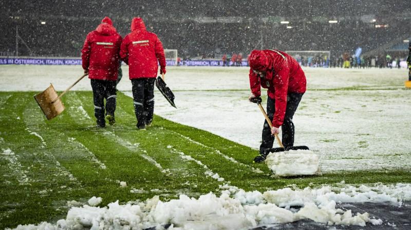 Strādnieki attīra laukumu no sniega Vācijas Bundeslīgas spēlē. Foto: www.imago-images.de/Scanpix